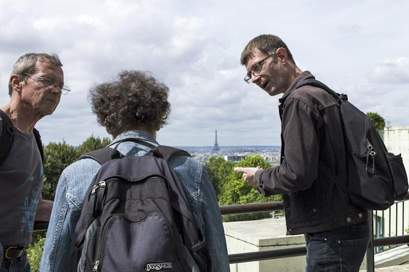 Vincent (R), a 39-year-old homeless man, speaks to tourists during a guided tour in Paris, on August 9, 2014