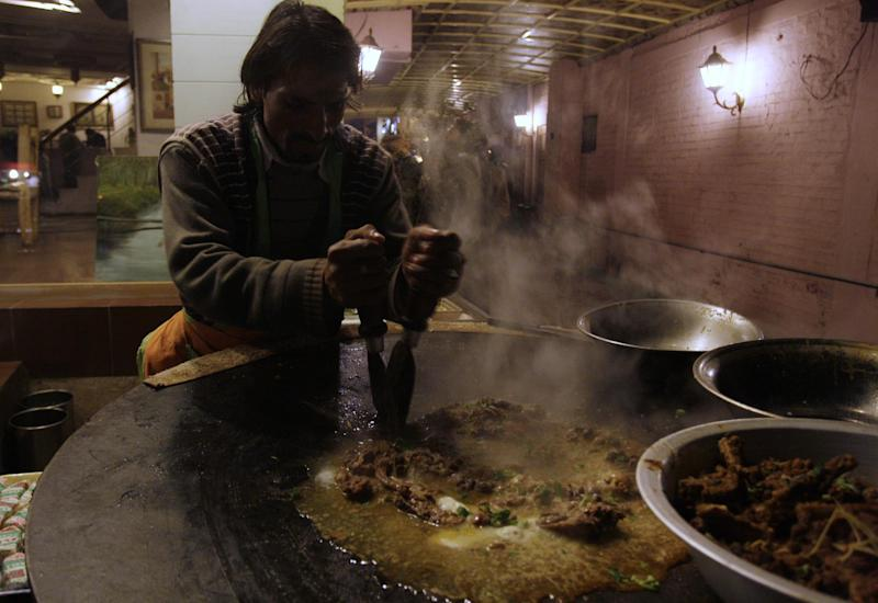 In this Saturday, Jan. 28, 2012 photo, a Pakistani chef prepares a traditional dish at Lahore's food park in Pakistan. Archenemies Pakistan and India have competed in a dangerous nuclear arm race, are going head-to-head for the first time in a pair of reality TV shows that pit chefs and musicians from the two countries against each other. (AP Photo/K.M.Chaudary)
