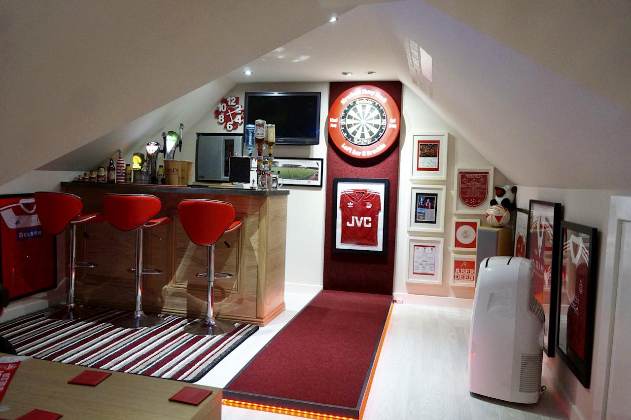 <p>It comes complete with a well-stocked bar with draught beer pumps, two TVs, and decked out in the team's red-and-white colours. </p>