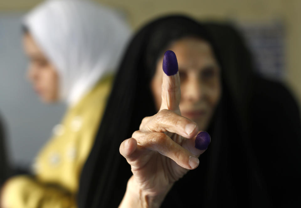 An Iraqi elderly woman shows her ink-stained finger after casting her vote inside a polling station in the country's parliamentary elections in Baghdad, Iraq, Sunday, Oct. 10, 2021. Iraq closed its airspace and land border crossings on Sunday as voters headed to the polls to elect a parliament that many hope will deliver much needed reforms after decades of conflict and mismanagement. (AP Photo/Hadi Mizban)