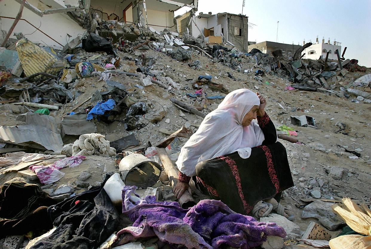 A Palestinian woman breaks down in tears trying to salvage usable belongings from her demolished house in the northern Gaza Strip refugee camp of Jabalia on Oct. 16, 2004.