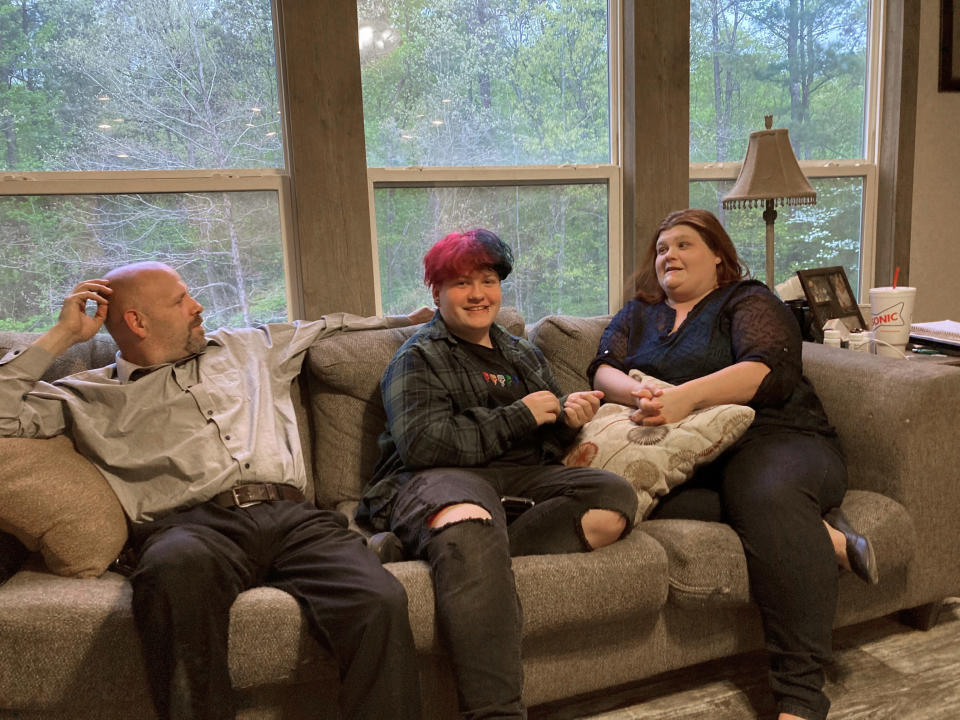 FILE - In this Thursday, April 15, 2021, file photo, Andrew Bostad, center, talks with his mother, Brandi Evans, and stepdad, Jimmy Evans, at their home in Bauxite, Ark. Andrew is one of hundreds of transgender youth in Arkansas who could have their hormone therapy cut off under a new state law banning gender confirming treatments for minors. On Tuesday, May 25, 2021, the American Civil Liberties Union asked a federal judge to strike down a new Arkansas law that made the state the first to ban gender confirming treatments or surgery for transgender youth. (AP Photo/Andrew DeMillo, File)