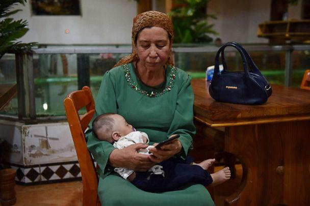 PHOTO: This file photo taken on May 31, 2019, shows a Uighur woman holding a baby in a Uighur restaurant in Hotan in China's northwest Xinjiang region. (Greg Baker/AFP via Getty Images)