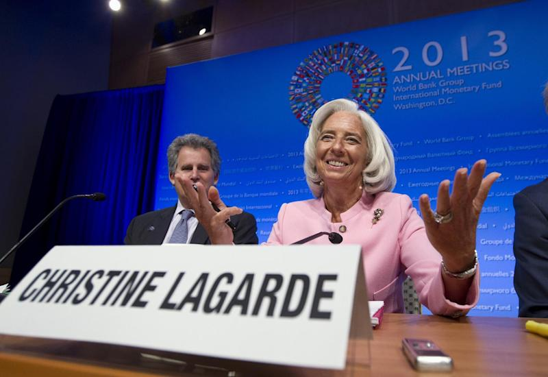 International Monetary Fund (IMF) Managing Director Christine Lagarde, right, accompanied by IMF First Deputy Managing Director David Lipton, gestures while speaking at a news conference during the World Bank/IMF Annual Meetings at IMF headquarters in Washington, Thursday, Oct. 10, 2013. Lagarde said the global economy is in a slow and unbalanced recovery, and warned that US failure to raise the debt ceiling because of impasse over the government shutdown would seriously damage the American as well as the global economy. (AP Photo/Jose Luis Magana)