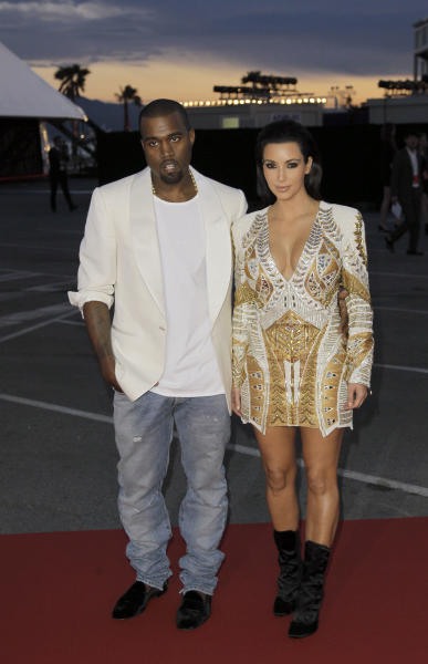 Singer Kanye West, left, and television personality Kim Kardashian arrive for the screening of Cruel Summer at the 65th international film festival, in Cannes, southern France, Wednesday, May 23, 2012. (AP Photo/Francois Mori)