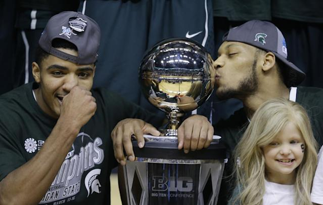 Michigan State's Gary Harris, left, poses with the championship trophy as Adreian Payne kisses it after they defeated Michigan 69-55 in an NCAA college basketball game in the championship of the Big Ten Conference tournament on Sunday, March 16, 2014, in Indianapolis. (AP Photo/Michael Conroy)