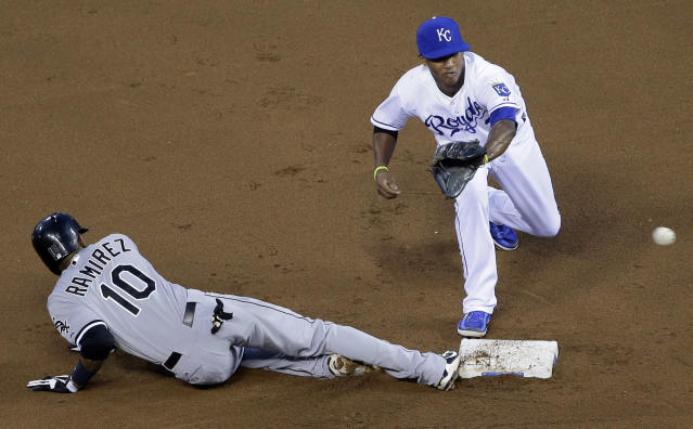 Chicago White Sox's Alexei Ramirez, left, beats the tag by Kansas City Royals shortstop Alcides Escobar while sliding back to second on a pickoff-attempt during the fourth inning of a baseball game on Wednesday, Aug. 21, 2013, in Kansas City, Mo. (AP Photo/Charlie Riedel)