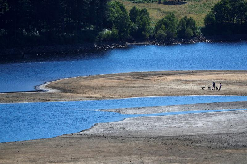 FILE PHOTO: Two people take a walk near the water's edge, where the water level has dropped significantly during the U.K. heatwave, of Torside Reservoir in Longdendale