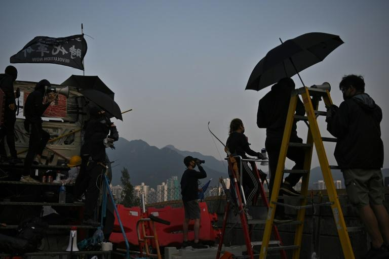 """Protesters stand on an observation point on a bridge over the Tolo Highway as they gather at the Chinese University of Hong Kong amid a """"blossom everywhere"""" campaign of road blocks and vandalism across the city"""