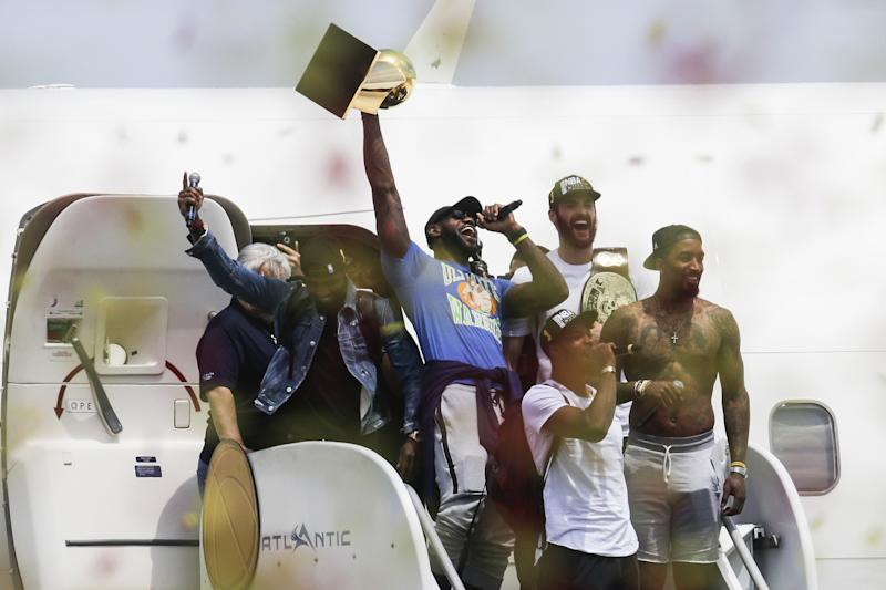 Cleveland Cavaliers' Lebron James, center, holds up the NBA Championship trophy alongside teammates Kyrie Irving, left, Kevin Love, rear right, J.R. Smith, right, and Tristan Thompson, front, at the airport in Cleveland, Monday, June 20, 2016. (AP Photo/John Minchillo)