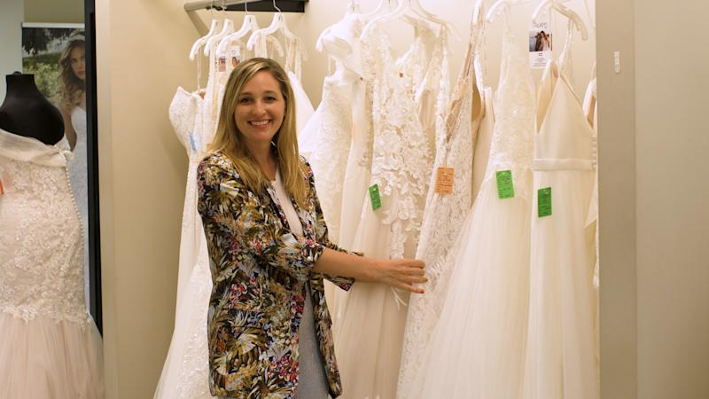 Jen Glantz – CEO & founder of Bridesmaid for Hire – holding on to a wedding dress at RK Bridal. (Source: Yahoo Finance)