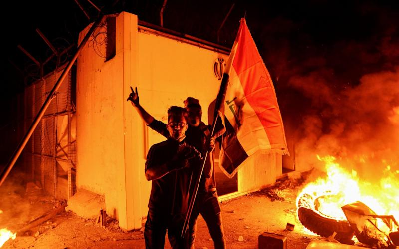 Iraqi demonstrators wave the Iraqi flag as flames consume Iran's consulate in the southern Iraqi Shia holy city of Najaf on Wednesday night - AFP