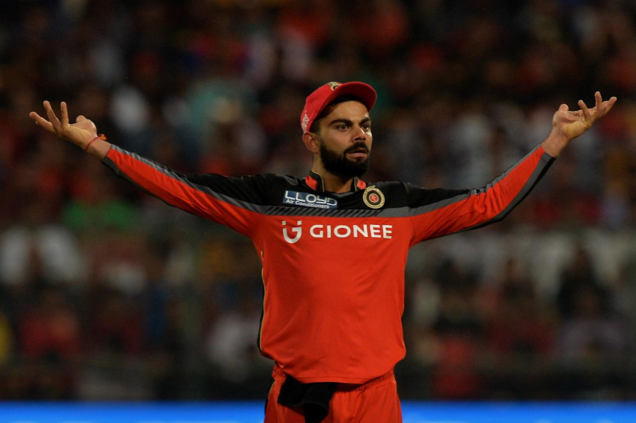 <p>Royal Challengers Bangalore captain Virat Kohli gestures during the 2017 Indian Premier League (IPL) Twenty20 cricket match between Royal Challengers Bangalore and Mumbai Indians at The M.Chinnaswamy Stadium in Bangalore on April 14, 2017. </p>