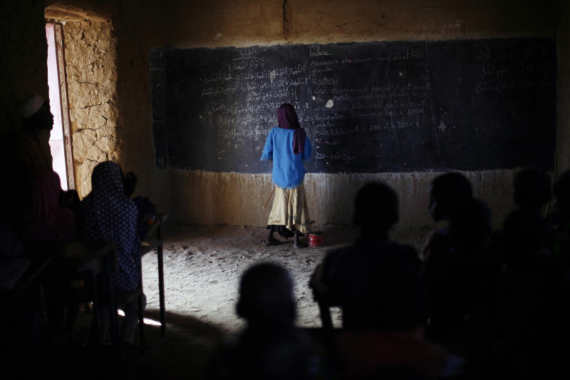 A Malian schoolgirl stands at the blackboard as schools reopen in Gao, northern Mali, Monday Feb. 18, 2013. (AP Photo/Jerome Delay)