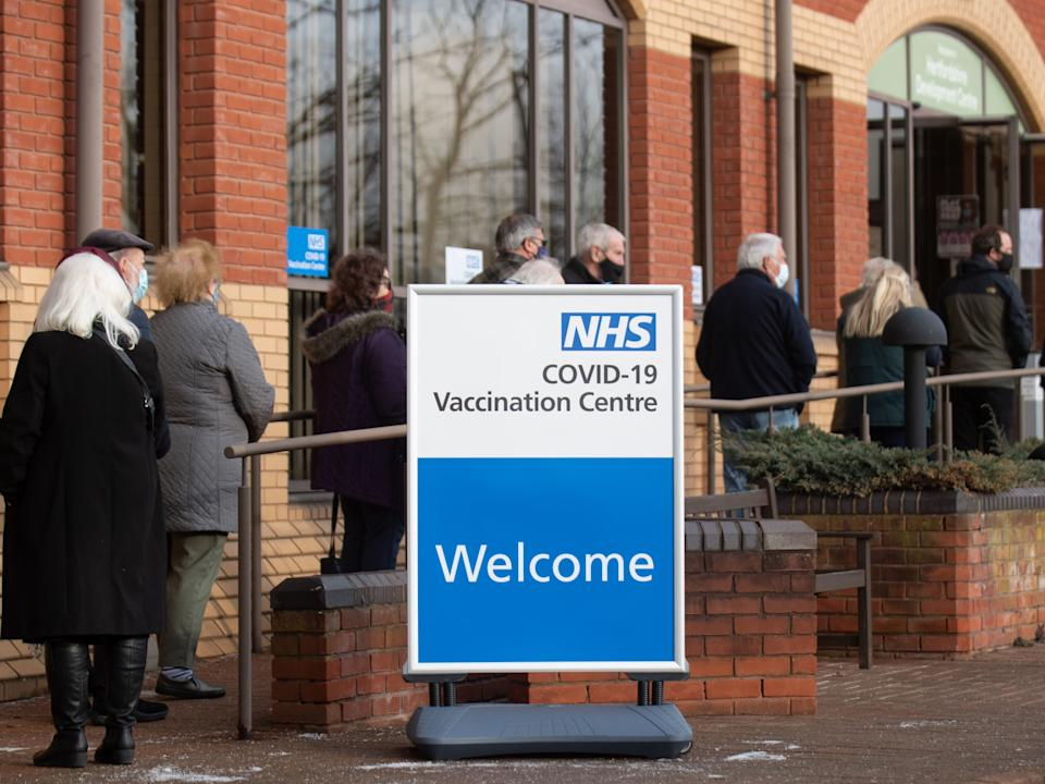 <p>People queue outside an NHS mass vaccination centre in Stevenage, one of several opening this week, to receive a Covid-19 jab</p> (Getty)