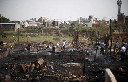 A man walks through the site after a fire broke out in a Rohingya camp in New Delhi