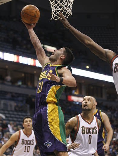 New Orleans Hornets' Greivis Vasquez (21) puts up a shot against Milwaukee Bucks' Drew Gooden (0) and Carlos Delfino (10) during the first half of an NBA basketball game on Wednesday, Feb. 15, 2012, in Milwaukee. (AP Photo/Jeffrey Phelps)