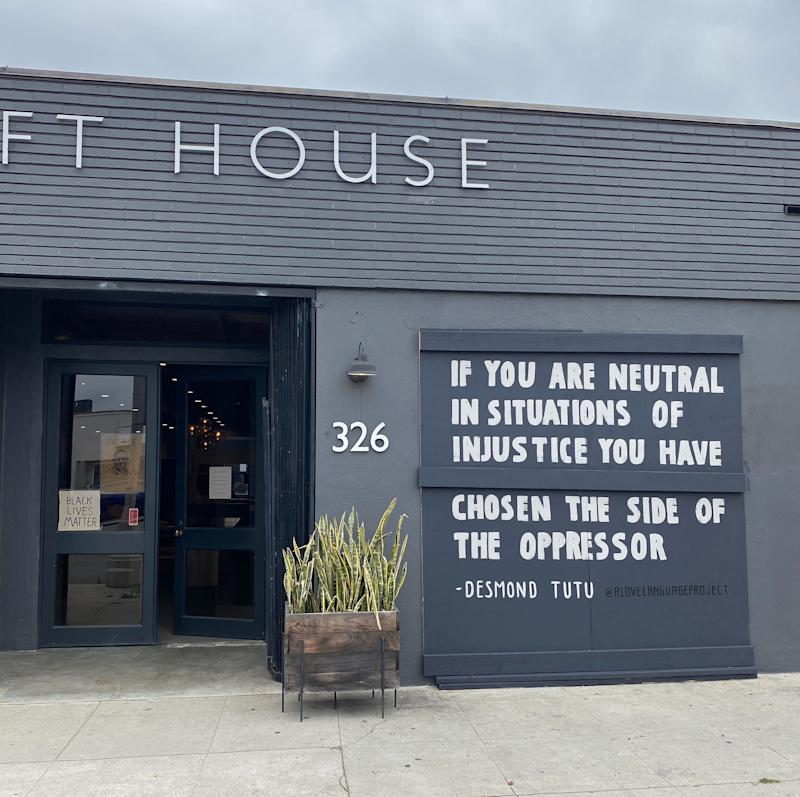 A Love Language Project has been using storefronts and walls to amplify black voices. They created quote murals on Croft House's boarded-up windows (Alex Segal)