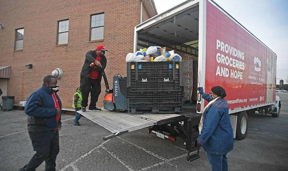 Volunteers from Greater Salem Church help unload a truck from Loaves & Fishes for a mobile food pantry distribution site on Tuesday, November 24, 2020.