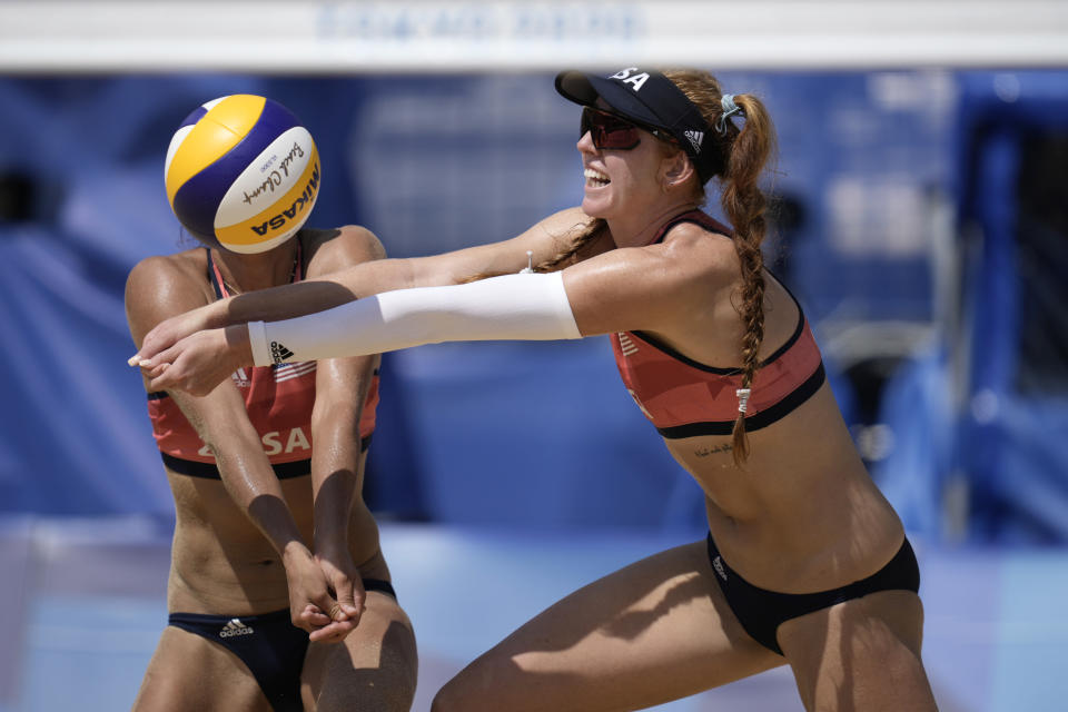 Kelly Claes, right of the United States, and teammate Sarah Sponcil converge to return a shot during a women's beach volleyball match against Canada at the 2020 Summer Olympics, Sunday, Aug. 1, 2021, in Tokyo, Japan. (AP Photo/Felipe Dana)