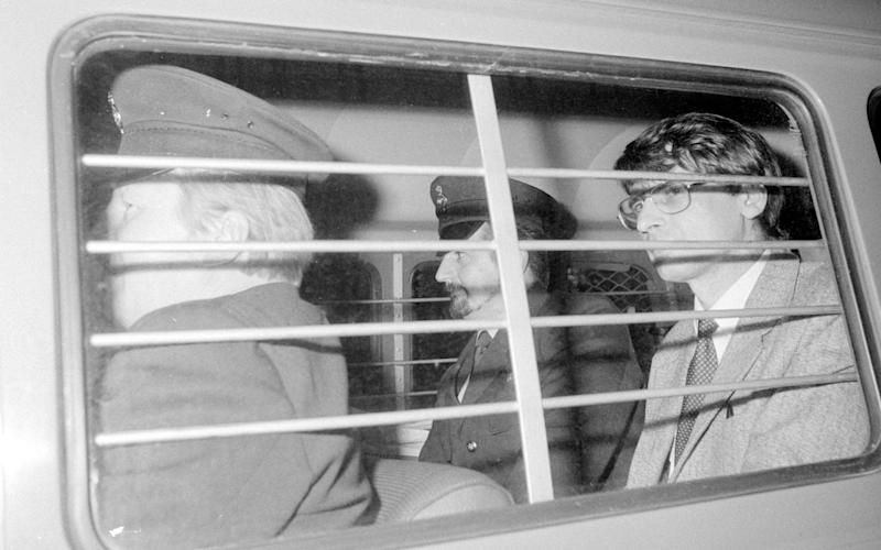 Serial killer Dennis Nilsen is escorted to a court hearing. He told police he killed as many as 15 people - PA