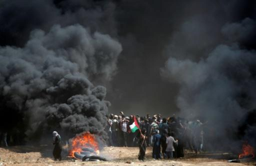 Palestinians protest during clashes with Israeli forces near the Gaza border on May 14, 2018
