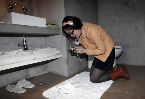 Ms. Zhuang, a Hotel Test Sleeper, takes a picture of slippers in the toilet of a boutique hotel in central Beijing March 6, 2012.