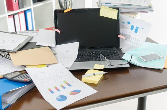 A cluttered desk with papers, a calculator, a stack of Post-its with a pen on top, and a smartphone around it, as well as a pair of glasses on top of it.