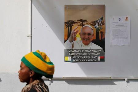 A woman walks past a portrait of Pope Francis at the Akamasoa community in Antananarivo