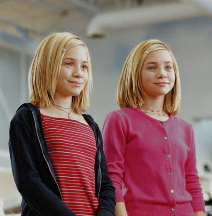 <p>We can't tell who is who, but both Mary-Kate and Ashley Olsen look cool here with their deep side parts and clips in <em>Switching Goals</em>. </p>