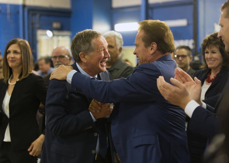 Republican centrist, Ohio Gov. John Kasich, and former California Gov. Arnold Schwarzenegger embrace at the first New Way California Summit, a political committee eager to reshape the state GOP, at the Hollenbeck Youth Center in Los Angeles Wednesday, March 21, 2018. (AP Photo/Damian Dovarganes)