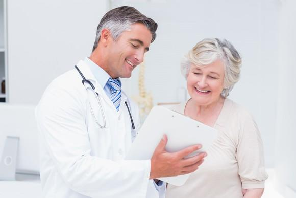 Doctor showing a clipboard to a happy patient.