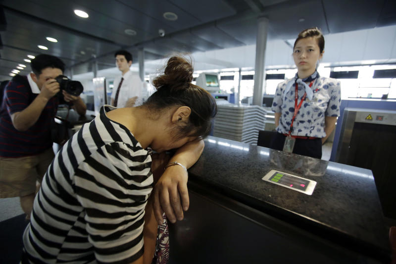 FILE - In this July 8, 2013 file photo, an unidentified family member of one of two Chinese students killed in a crash of an Asiana Airlines' plane on Saturday, cries at the airline's counter as she and other family members check in for a flight to San Francisco, at Pudong International Airport in Shanghai, China. In the first investigation of its kind, federal transportation officials are reviewing whether Asiana Airlines failed to meet legal obligations to help the families of passengers after one of its planes crashed at San Francisco International Airport, killing three people. Under U.S. law, Asiana was required to provide a range of services to family members of the 291 passengers, from the prompt posting of a toll-free number to gather and distribute information, to providing transportation and lodging so family members can comfort injured loved ones. (AP Photo/Eugene Hoshiko, File)