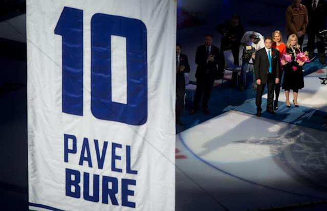 Retired Vancouver Canucks forward Pavel Bure, left, of Russia, watches with his wife Alina Khasanova, center, and mother Tatiana Bure as his number 10 is retired during a ceremony before the Canucks NHL hockey game against the Toronto Maple Leafs in Vancouver, British Columbia, on Saturday Nov. 2, 2013. (AP Photo/The Canadian Press, Darryl Dyck)