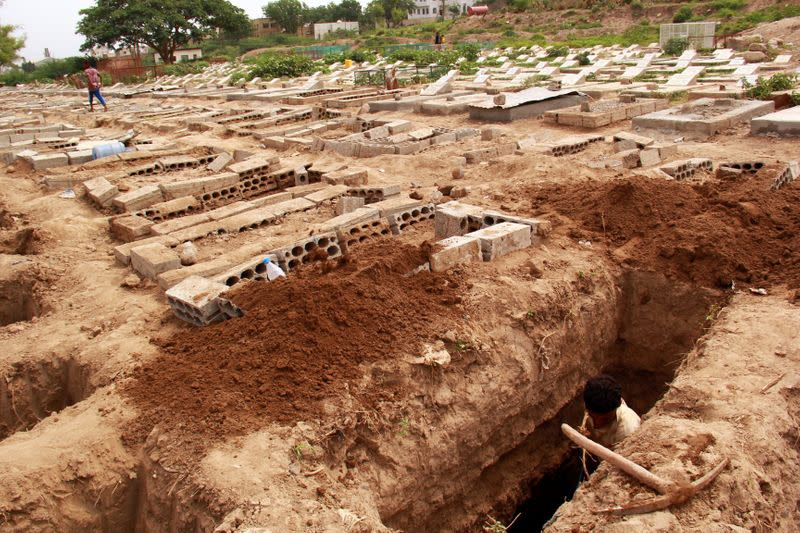 FILE PHOTO: A man digs a grave at a cemetery where victims of the coronavirus disease (COVID-19) are buried in Taiz
