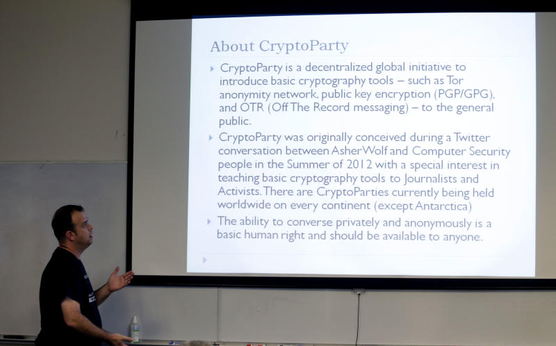 """In this Thursday, July 18, 2013, photo, information technology professional Josh Scott looks up at a visual he uses while hosting a monthly """"Cryptoparty"""" in Dallas. Across the Internet, users are talking about changes small and large, from using more encryption and stronger passwords to much more extreme measures such as ditching cellphones and using cash over credit cards. The conversations play out daily on Reddit, Twitter and other networks, and have spread to offline life with so-called """"Cryptoparty"""" gatherings in cities including Dallas, Atlanta and Oakland, Calif. (AP Photo/LM Otero)"""
