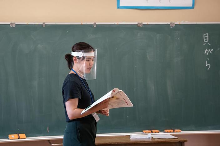 "<div class=""inline-image__caption""> <p>A teacher wears a plastic face visor at Kinugawa Elementary School in Nikko, Japan. </p> </div> <div class=""inline-image__credit""> Carl Court/Getty </div>"