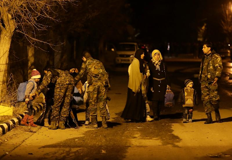 Syrians are helped by members of the government forces on the outskirts of the besieged rebel-held town of Madaya, on January 11, 2016 (AFP Photo/Louai Beshara)
