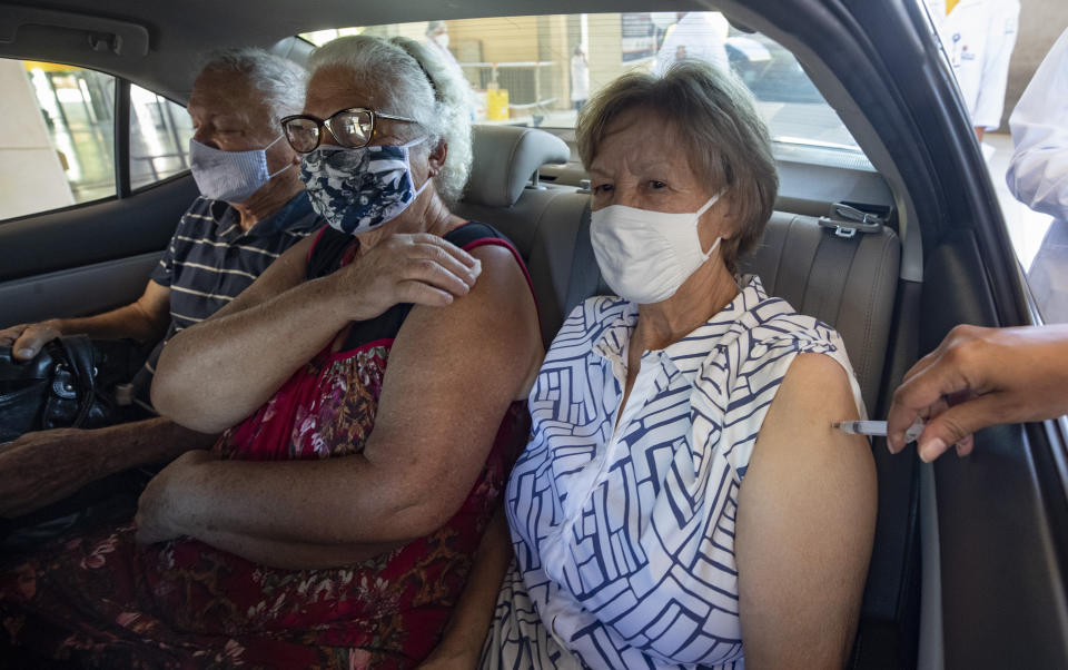 Three people in a car get their shots of the Sinovac COVID-19 vaccine at a drive-thru site set up in the Pacaembu soccer stadium parking lot as part of a priority vaccination program for seniors in Sao Paulo, Brazil, Wednesday, March 3, 2021. (AP Photo/Andre Penner)