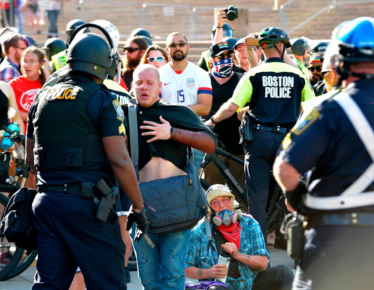 Protesters are overcome after police used pepper spray on anti-parade demonstrators during the