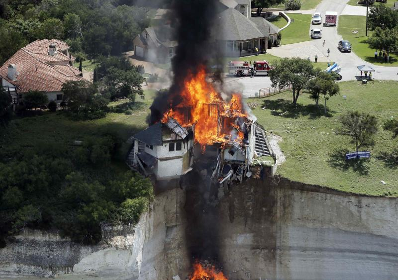 Smoke rises from a house deliberately set on fire, days after part of the ground it was resting on collapsed into Lake Whitney, Texas June 13, 2014. Building crews set fire on Friday to the luxury lake house left dangling about 75 feet (23 meters) on a decaying cliff that has been giving way underneath the structure. REUTERS/Brandon Wade (UNITED STATES - Tags: REAL ESTATE BUSINESS SOCIETY)