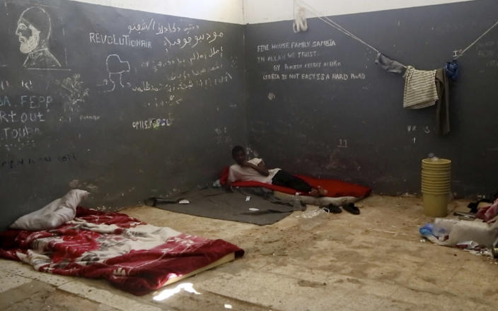 In this Wednesday, July 17, 2019 frame grab from video, a migrant rests in a detention center in the city of Sabha, which is about 650 kilometers, or 400 miles, south of the capital, Tripoli, Libya. Migrants held at a small, dilapidated detention center in the southern Libyan city of Sabha say they are being neglected by international organizations and often go hungry due to lack of food. (AP Photo)