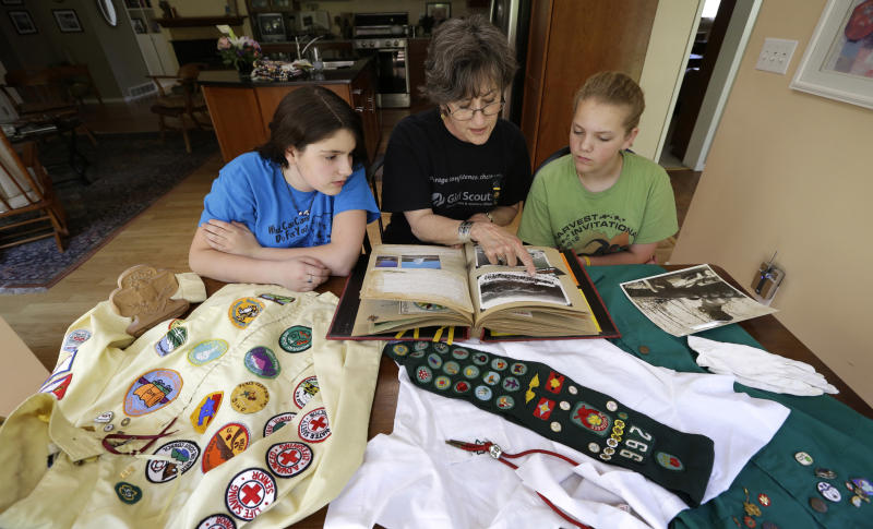 In this Tuesday, May 14, 2013 photo, Joni Kinsey, of Iowa City, Iowa, shows some of her Girl Scouts memorabilia to two girls in her troop in Iowa City, Iowa. In an effort to save money, Girl Scout councils across the country are making proposals that would have been unthinkable a generation ago: selling summer camps that date back to the 1950s. (AP Photo/Charlie Neibergall)