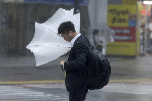 A man struggles with his umbrella against strong wind at a crossing in Shibuya district, Tokyo Saturday, Oct. 12, 2019. Tokyo and surrounding areas braced for a powerful typhoon forecast as the worst in six decades, with streets and trains stations unusually quiet Saturday as rain poured over the city. (AP Photo/Kiichiro Sato)