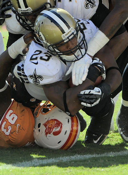 New Orleans Saints running back Pierre Thomas (23) pushes over Tampa Bay Buccaneers defensive tackle Gerald McCoy (93) for a touchdown during the fourth quarter of an NFL football game Sunday, Oct. 21, 2012, in Tampa, Fla. (AP Photo/Brian Blanco)