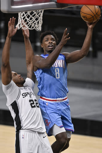 Houston Rockets' Jae'Sean Tate (8) shoots as he is defended by San Antonio Spurs' Rudy Gay during the second half of an NBA basketball game, Saturday, Jan. 16, 2021, in San Antonio. (AP Photo/Darren Abate)