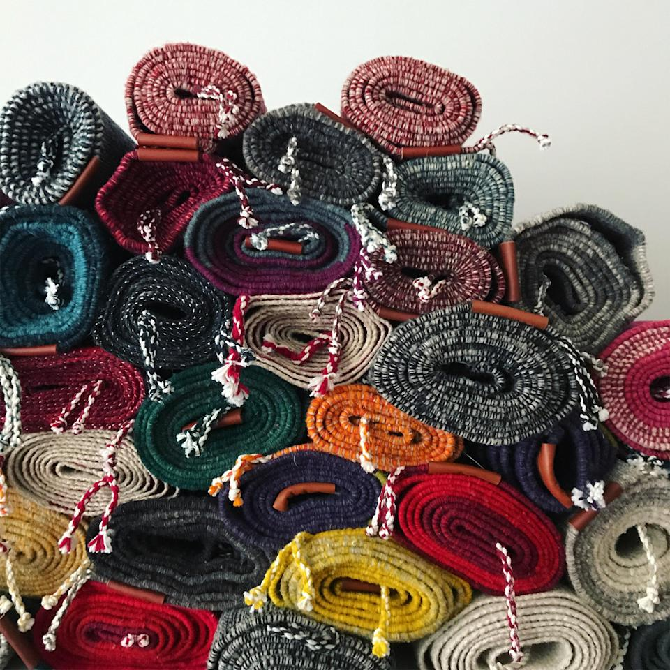 A pile of woven rugs at Estudio Pomelo