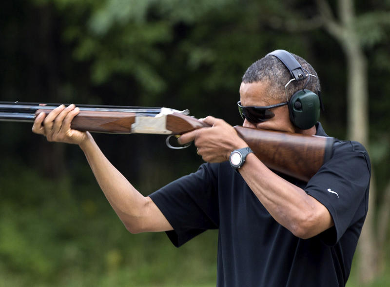 """In this photo released by the White House, President Barack Obama shoots clay targets on the range at Camp David, Md., Saturday, Aug. 4, 2012. The White House released a photo of Obama firing a gun, two days before he heads to Minnesota to discuss gun control. In a recent interview with The New Republic magazine, Obama said yes when asked if he has ever fired a gun. He said """"we do skeet shooting all the time,"""" except for his daughters, at Camp David. (AP Photo/The White House, Pete Souza)"""