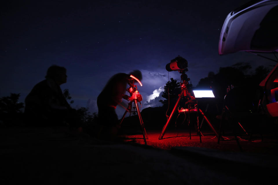 Astrophotographer Johnny Horne works under the night sky to photograph Comet NEOWISE as his wife Ann looks on at Grandfather Mountain in Linville, N.C., Friday, July 17, 2020. (AP Photo/Gerry Broome)