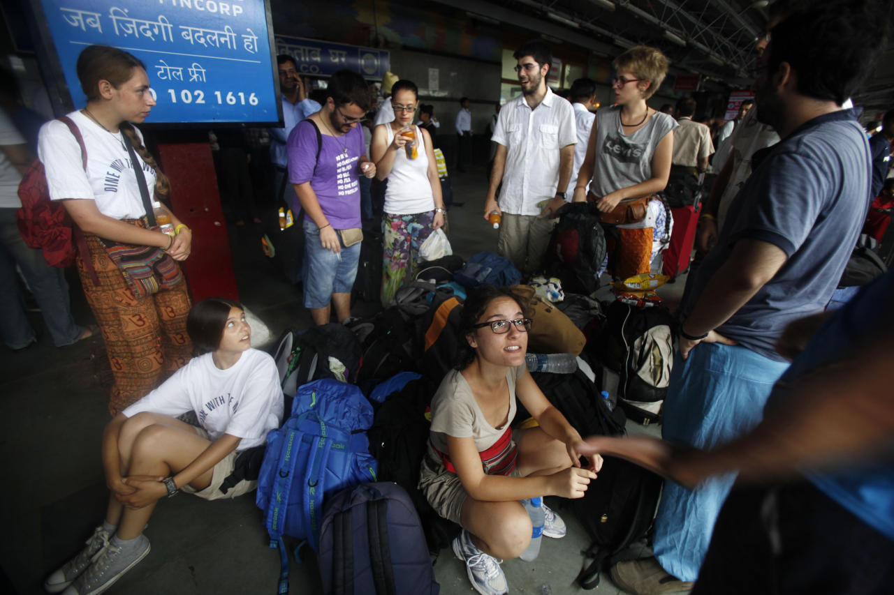 Stranded foreign passengers wait for their train at New Delhi railway station, in New Delhi, India, Monday, July 30, 2012. The electricity grid across northern India failed Monday, leaving hundreds of millions of people without electricity in one of the worst power failures of the past decade, officials said. (AP Photo/Rajesh Kumar Singh)